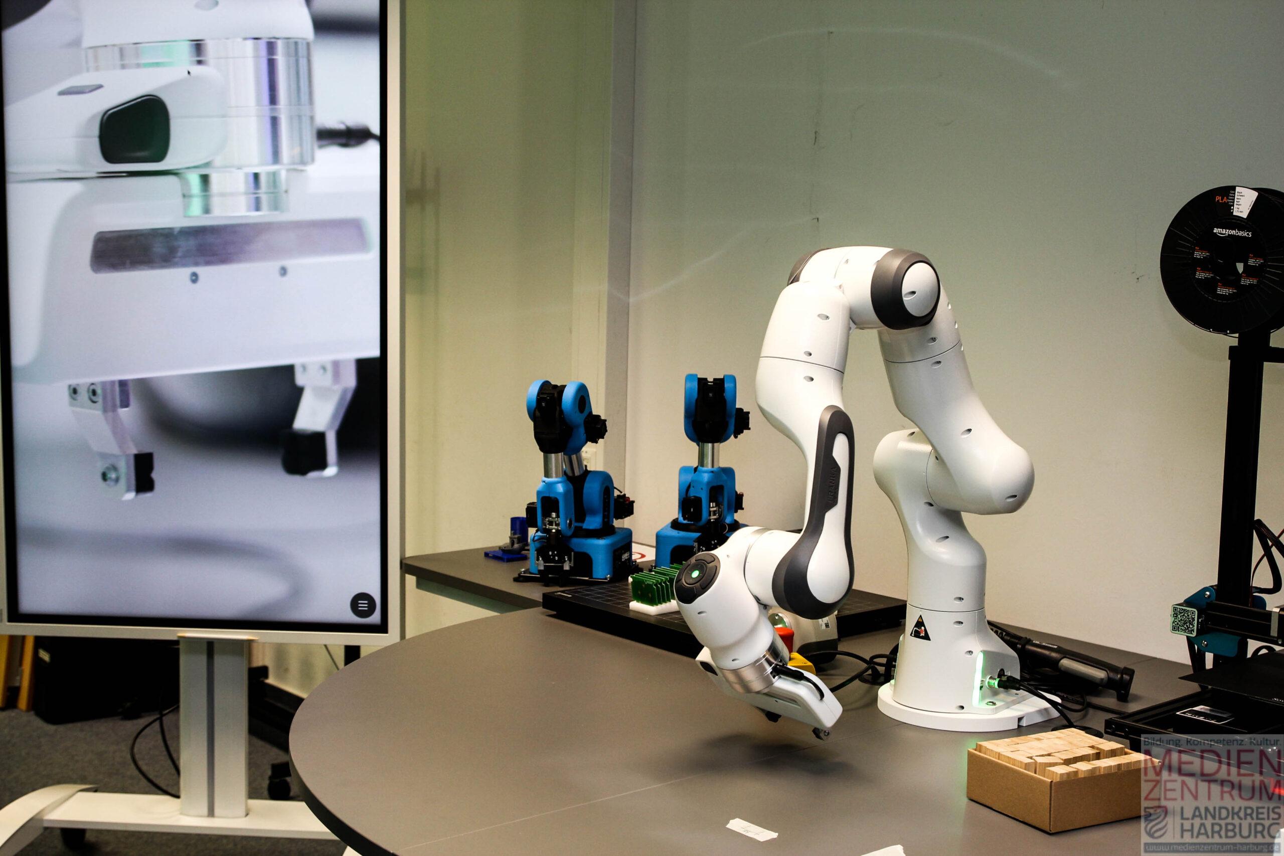 Rechts einer der 3D Drucker, daneben in der Mitte der weisse Panda. Links davon sind zwei Niryo Ned Roboter für den Gruppeneinsatz